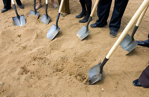 6 shovels on the ground for a ground breaking ceremony